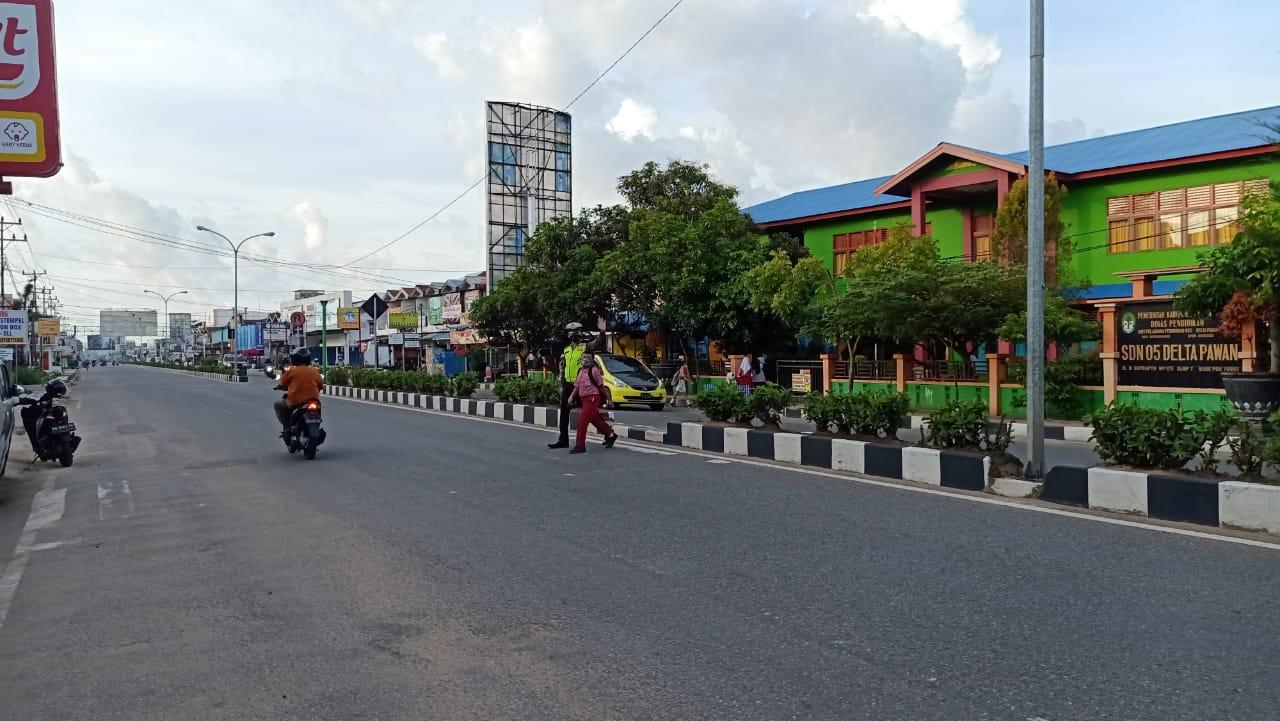 Jaga Keselamatan Polisi Bantu Anak Sekolah Menyebrang Jalan