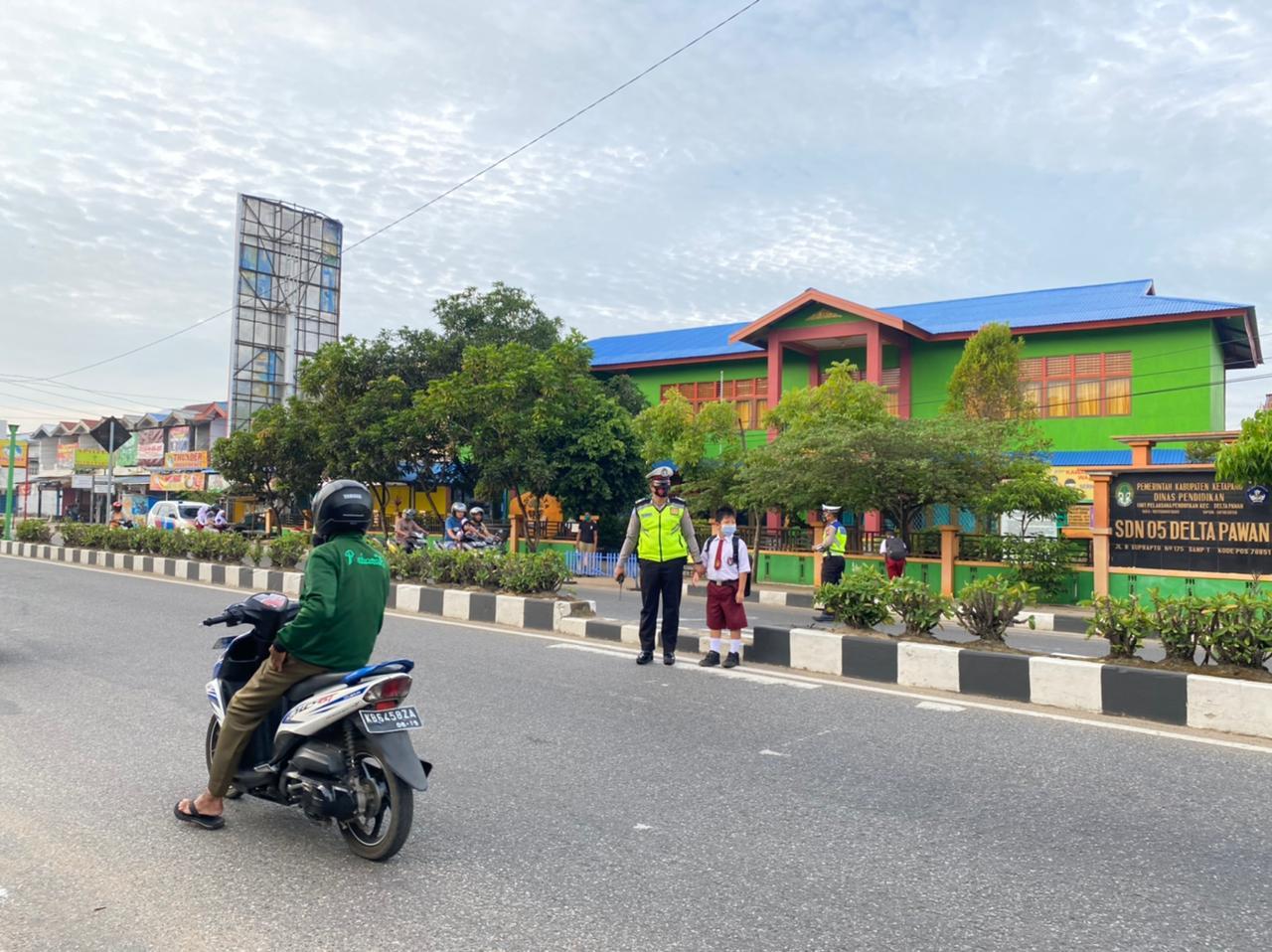 Personil Satlantas Polres Ketapang Seberangkan Anak Sekolah