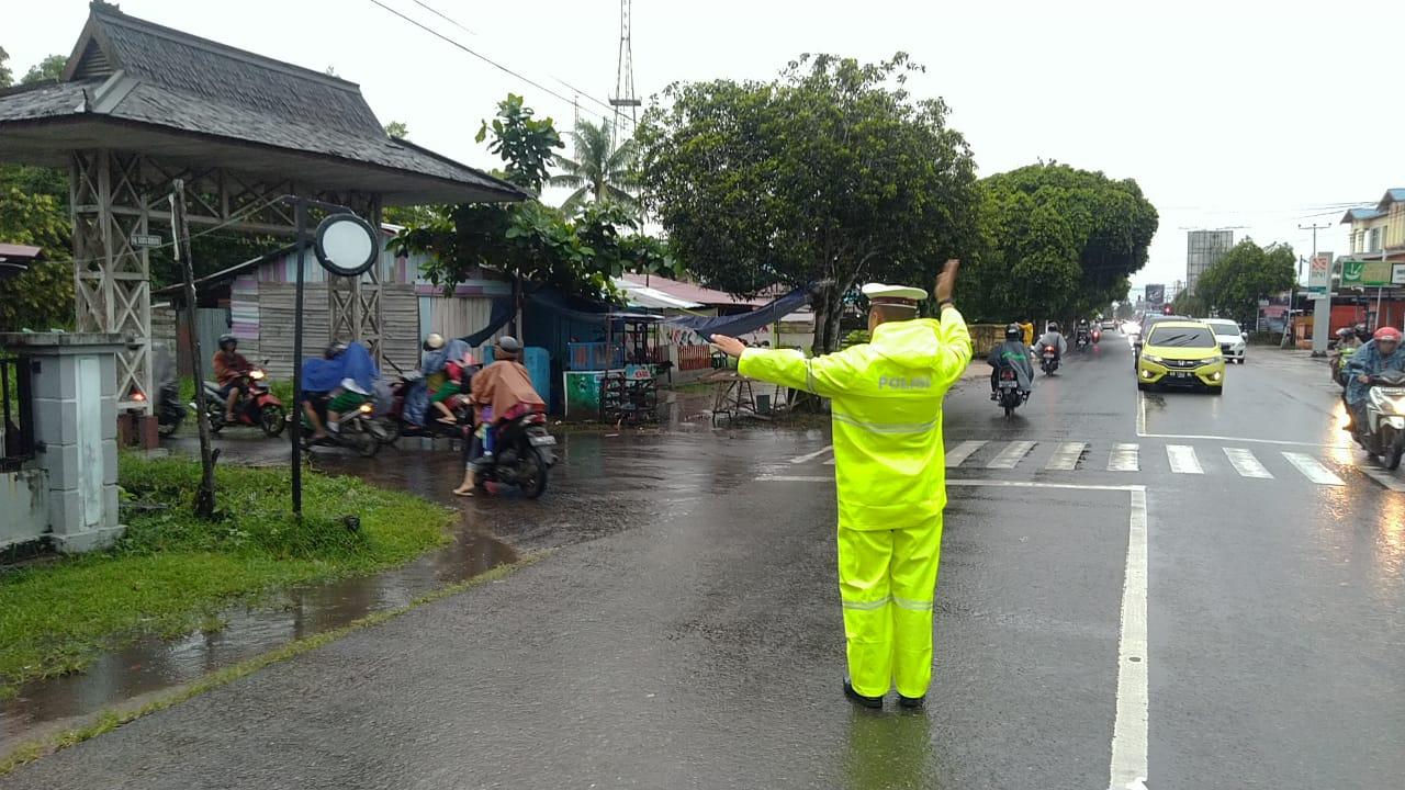 Diguyur Hujan, Personel Satlantas Polres Ketapang Tetap Semangat Atur Lalulintas