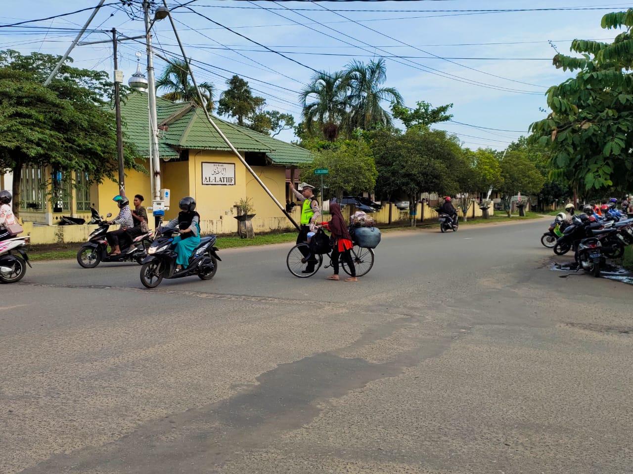 Anggota Sat Lantas Bantu Masyarakat Pengguna Sepeda Menyebrang Jalan