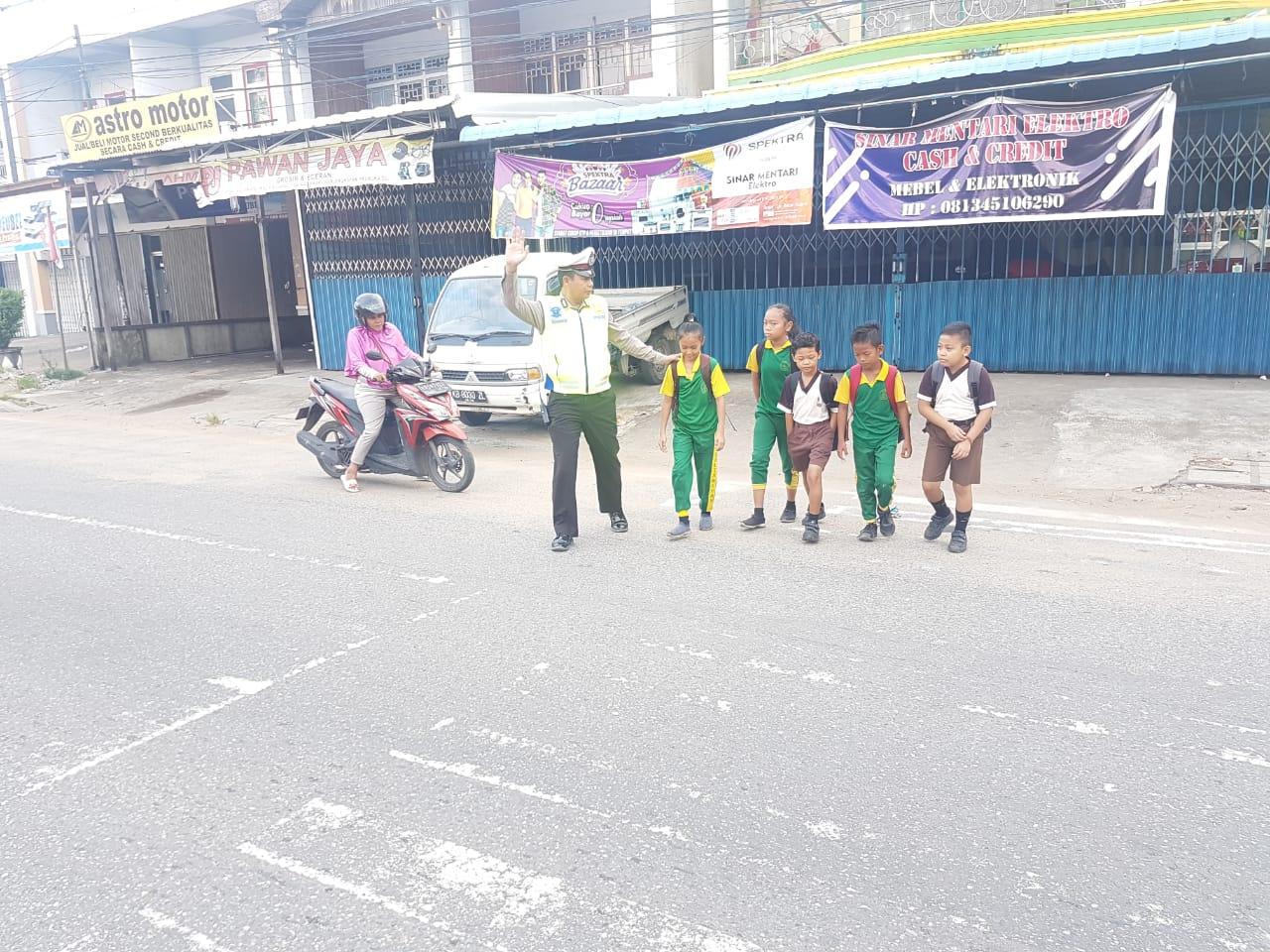 Ciptakan Kamseltibcar Di Jalan Raya, Aiptu Ruswanto Bantu Anak Sekolah Yang Akan Menyebrang Jalan