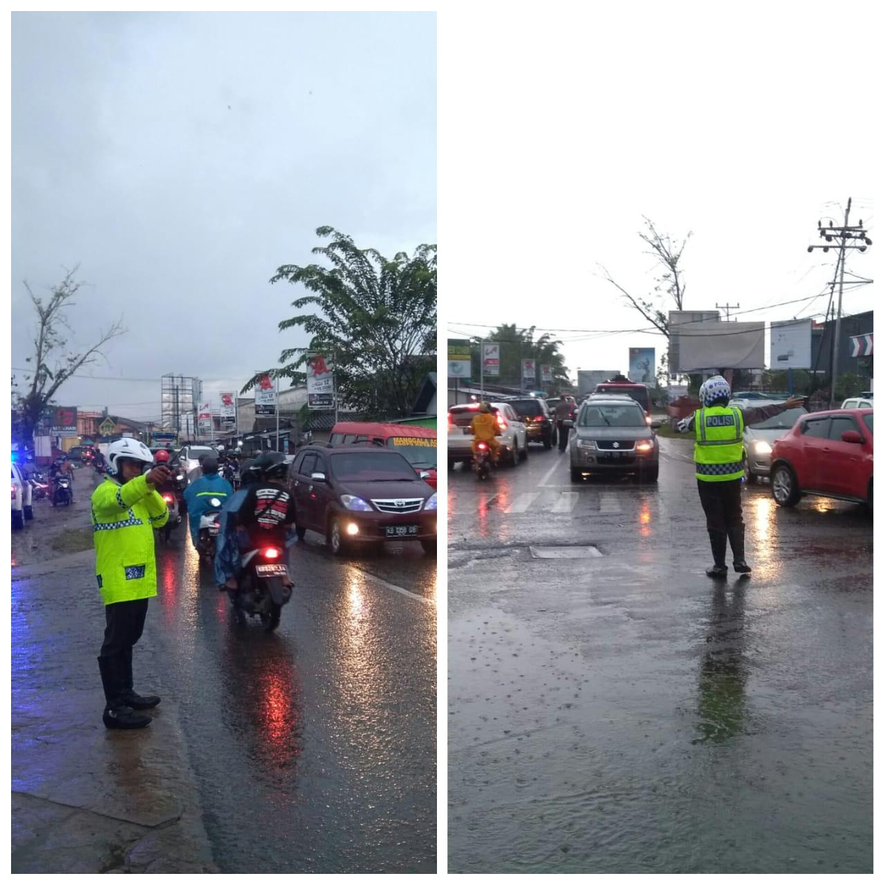 Hujan tidak menghalangi anggota lalu lintas polres ketapang melakukan pengaturan di jalan