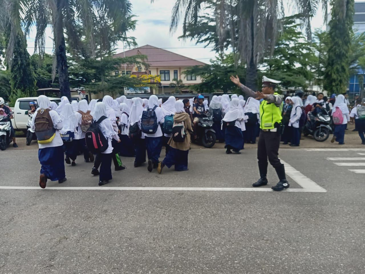 Selain Mengatur Lalin, Petugas Satlantas Polres Ketapang Juga Bantu Anak Sekolah Menyebrang Jalan